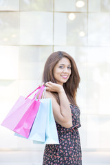 Portrait of elegant smiling woman holding shopping bags.