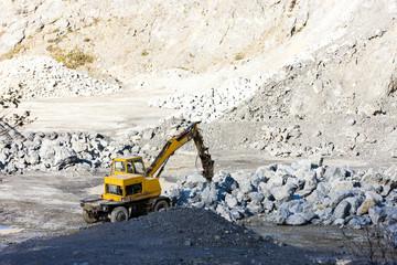 excavator loading rocks at quarry