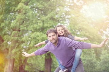 Vater und Tochter spielen Flieger in der Sonne