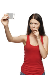 Discontent woman taking pictures of herself through cellphone
