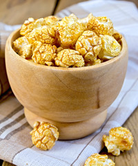Popcorn caramel in wooden bowl on board with napkin