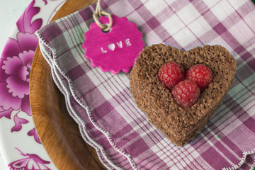 Heart of cake and raspberries, red card