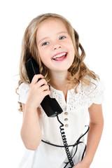 Adorable smiling little girl speaking by phone isolated
