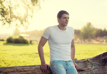 Handsome man outdoors, soft sunny sunset, man pensive looks away