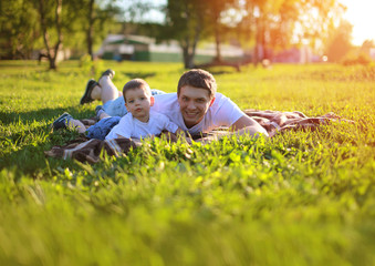 Happy father and son having fun lying on the grass in summer