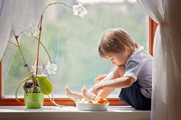 Cute little boy, sitting on the window, eating fruits