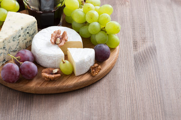 assorted cheeses and fresh grapes on the board