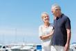 canvas print picture - glückliches, älteres paar geht am hafen entlang