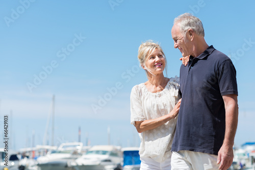 Leinwanddruck Bild glückliches, älteres paar geht am hafen entlang