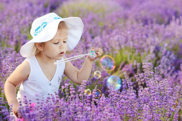 toddler in field with bubbles