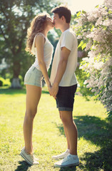Young couple in love, sensual kiss in sunny summer day