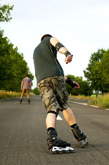Young man with inline skates in summer