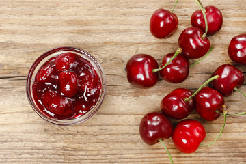 Bowl of cherry jam on wooden table