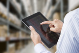 Businessman checking inventory in stock room on tablet