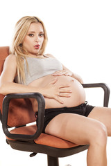 Tired pregnant woman sitting on a chair