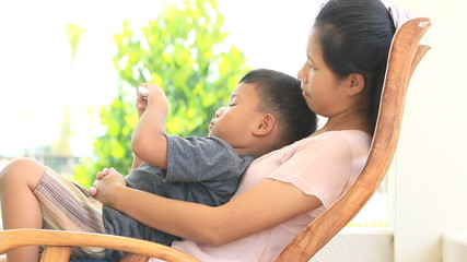 Mother and son enjoy sitting on rocking chair.
