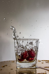 Cherry falls with a splash in a glass with water.