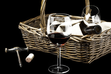The wine glass and picnic basket on a black
