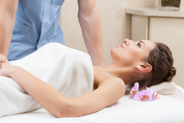 Woman wrapped in white towel lying on massage table
