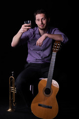 Guitar and trumpet player holding a glass of alcohol