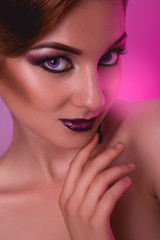 Portrait of voluptuous adult girl with make up on pink backgroun