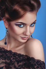 Luxury fashion woman with accessories and make up on blue backgr