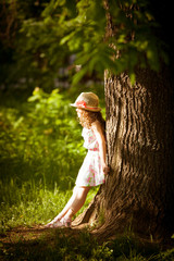 Girl stands near a tree in sunlight