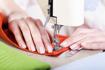 Neat tailor sewing a fabric