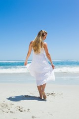 Pretty carefree blonde walking on the beach