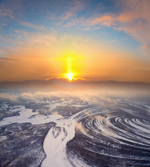 Bright sunrise over frozen plain in winter