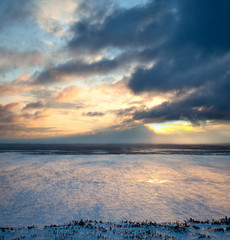 Windy sunset above frozen lake, top view