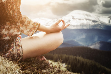 Young woman meditating in the mountains