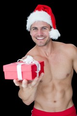 Smiling muscular man posing in sexy santa outfit offering gift
