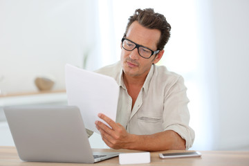 Mature man with eyeglasses working from home on laptop