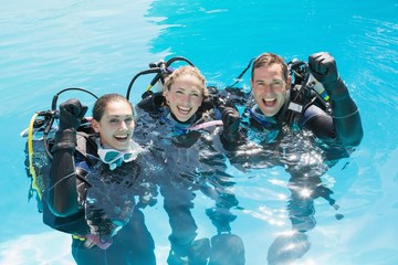 Smiling friends on scuba training in swimming pool cheering at c