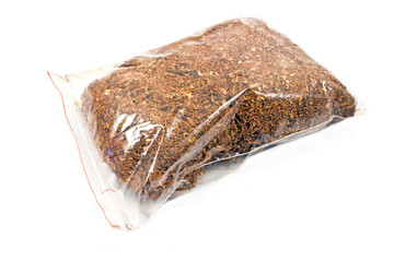 Pile of dried tobacco in plastic bag isolated on white