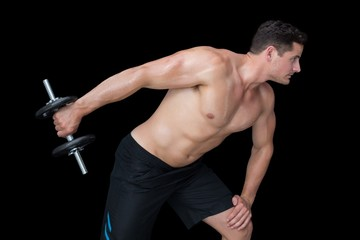 Strong crossfitter lifting heavy black dumbbell behind him
