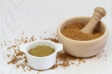 Mustard seeds in wooden mortar and mustard in white bowl