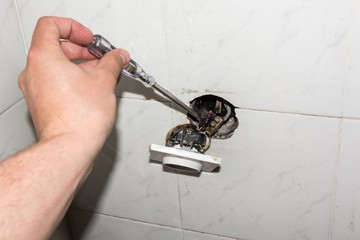 Hand holding a screwdriver pointing at a damaged electric socket