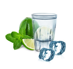 glass of vodka with lime, mint and ice cubes