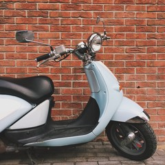 scooter near red brick wall