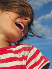 happy laughing child against blue sky