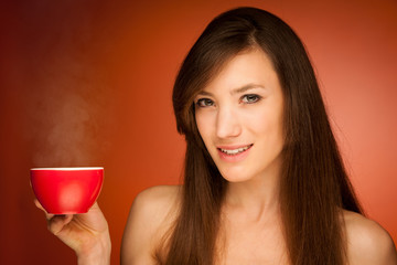 Beautiful young woman with cup of tea in her hands