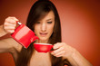 Beautiful young woman with tea pot and mug in her nhands