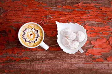 Mug of caramel chocolate latte with cookies