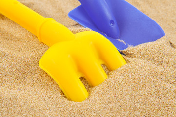 toy shovel and toy rake on the sand