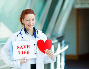 Doctor holding save life sign standing in hospital hallway