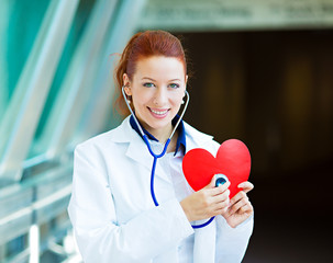Portrait happy doctor listening to heart with stethoscope