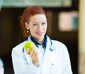 Doctor offering green apple standing in hospital hallway
