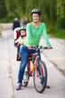 Caucasian young woman on a bicycle with little son behind